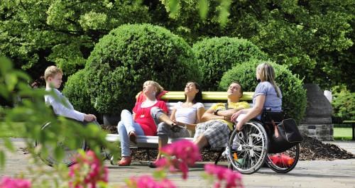 Junge Leute sitzen auf einer Parkbank und unterhalten sich mit Rollstuhlfahrern