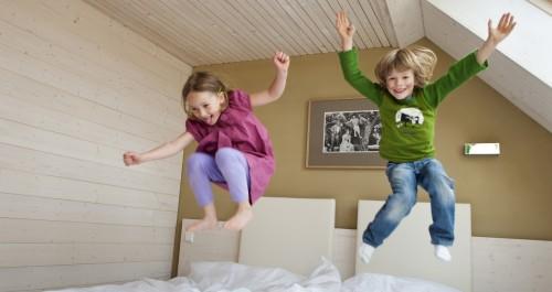 Kinder springen in Doppelbetten