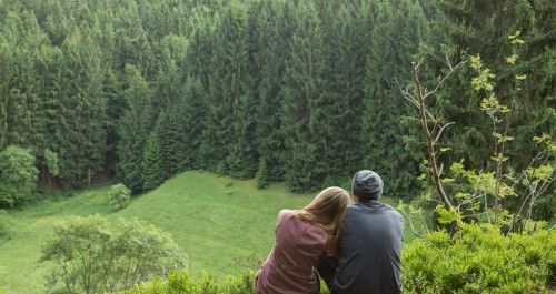 Pärchen sitzt auf der Bank und schaut ins Tal am Lutherweg