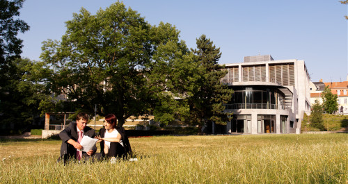 Zwei Personen sitzen im Gras vor Weimarhalle