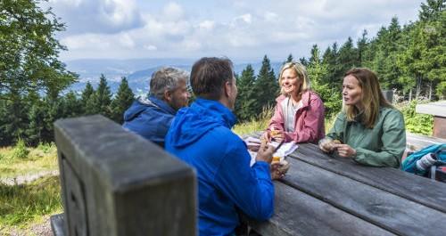 4 Wanderer sitzen an der Wanderrast am Rennsteig