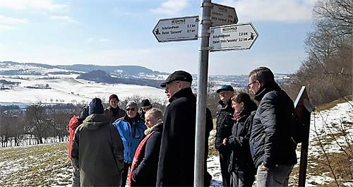 Wanderer stehen am Wegweiser und schauen in die Landschaft