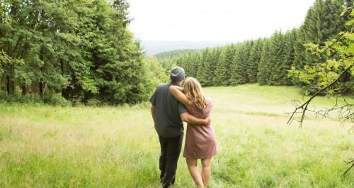 Zwei Personen stehen auf einer Wiese und schauen über den Thüringer Wald