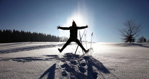 Person steht im Schnee vor der Sonne
