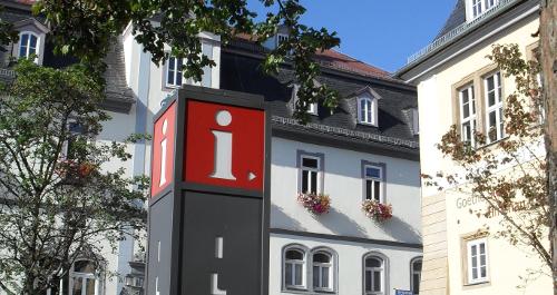 Säule mit weißem i auf rotem Grund vor Gebäuden