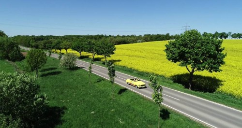 Fahrendes Auot auf der Straße zwischen gelb blühenden Rapsfeldern