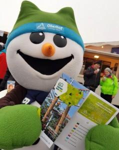 Das Oberhofer Maskottchen Flocke, ein Schneemann, hält beim Biathlon Weltcup 2020 den Erlebnisführer Thüringer Wald mit der Thüringer Wald Card in den Händen.