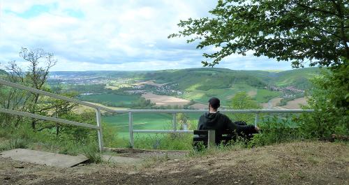 Wanderer sitzt auf Bank am Aussichtspunkt Hohe Lehde und blickt in das Saaletal