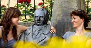 Mädchen sitzen auf einer Bank, gemeinsam mit Goethe