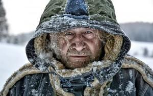 Ein Mann versteckt sich unter der Kapuze seines Wintermantels und ist gezeichnet von Eis an seinen Haar- und Bartspitzen.