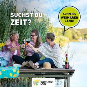 Drei Frauen sitzen in Hohenfelden am Stausee auf einem Steg und genießen ihren Urlaub und stoßen darauf an. Suchst du Zeit? Dann komm ins Weimarer Land.