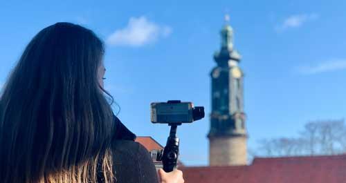 Online-Stadtführung Frau mit Handy und Denkmal im Hintergrund