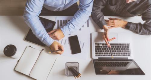 Männer arbeiten an Laptop und Telefon