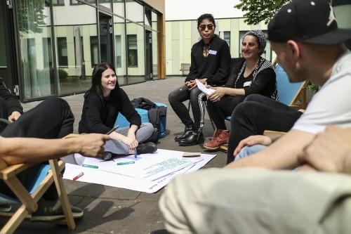 Junge Leute diskutieren während des Barcamp